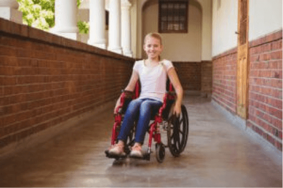 young girl in wheelchair in hall